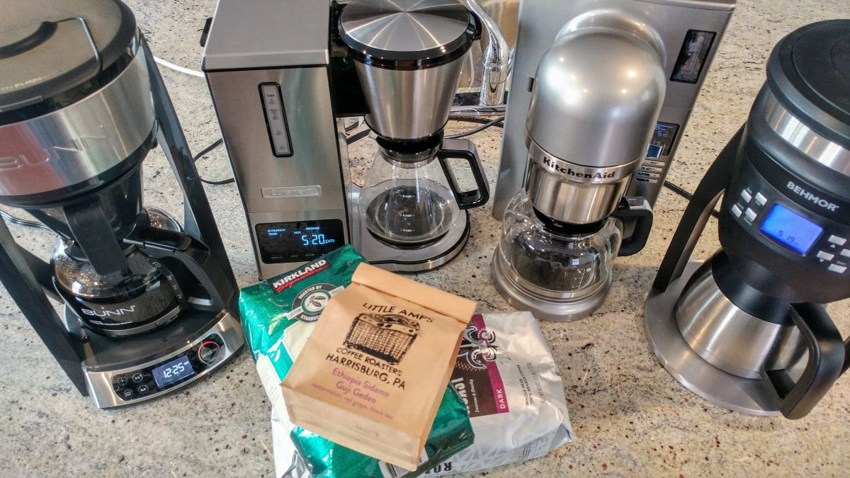 Four coffee makers (left to right: a Bunn HB, a Cuisinart CPO-800, a KitchenAid KCM0802, and a Behmor Brazen Plus) are arranged in a semicircle around three bags coffee.