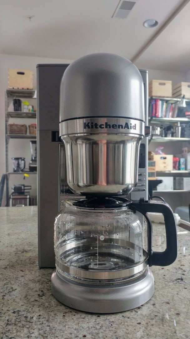 A front view of the KitchenAid KCM0802. Stylish kitchen shelving from Ikea is visible in the background.