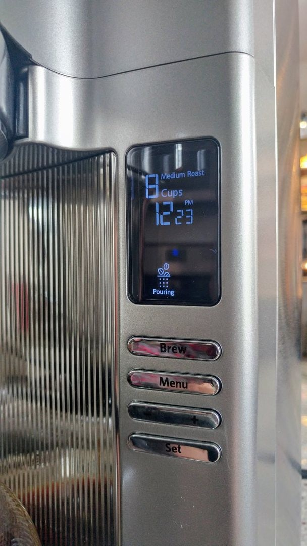 """A closeup of the display panel of the KCM0802. The display currently indicates that it's brewing 8 cups on medium roast, and is currently in the """"pouring"""" cycle."""