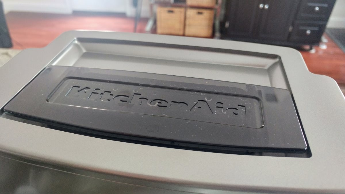 The top of the KCM0802. A plastic sliding lid stamped with the KitchenAid logo is currently closed, but can be slid open to fill the reservoir with water.