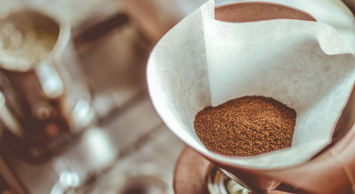 A Chemex filled with finely-ground coffee beans is being used to make coffee. A sink and metal pitcher are visible in the background.