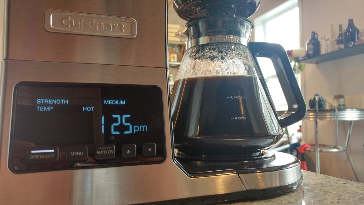 """A closeup of the CPO-800's vacuum fluorescent display. The display indicates the brew strength (""""medium""""), the brew temperature (""""hot""""), the time, and the fact that it's turned on."""