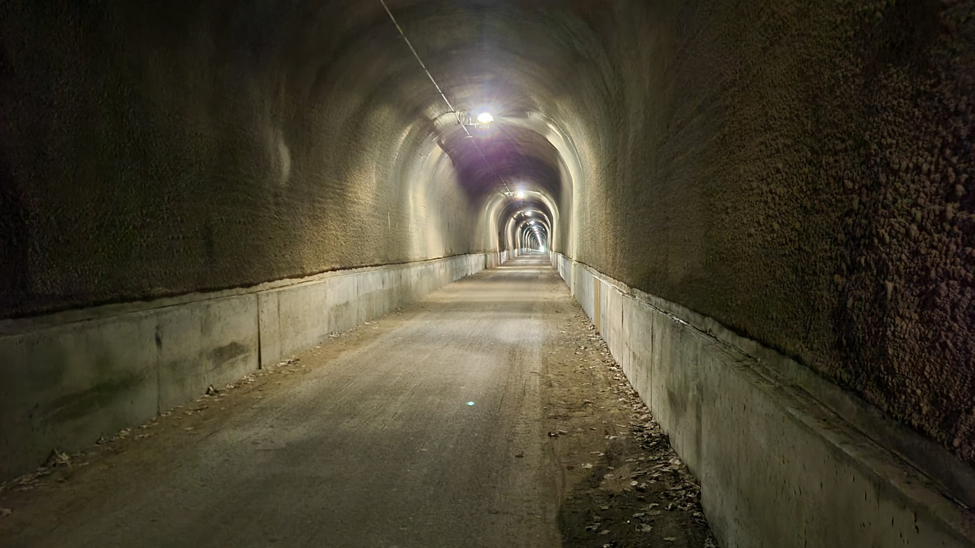 A long tunnel is lit by bright overhead lights.