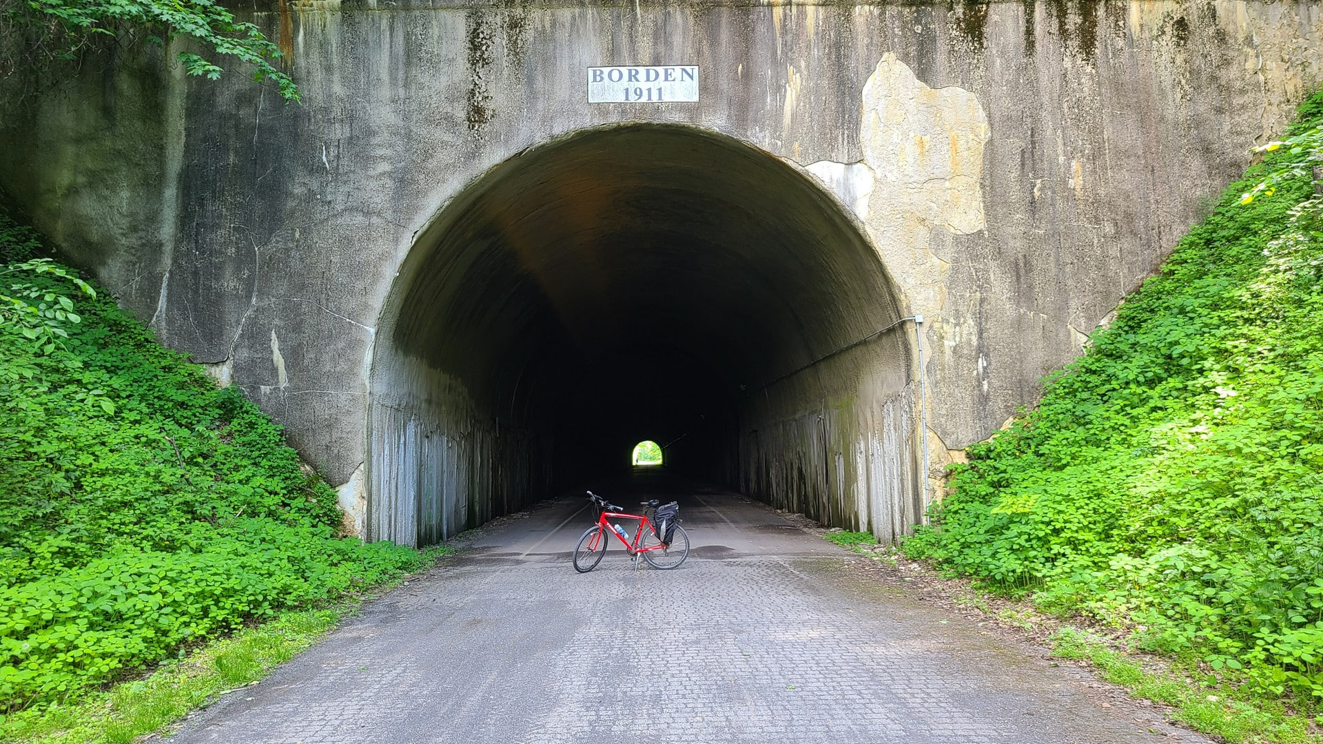 A red bike with a black and silver pannier stands across the entrance to a large tunnel.