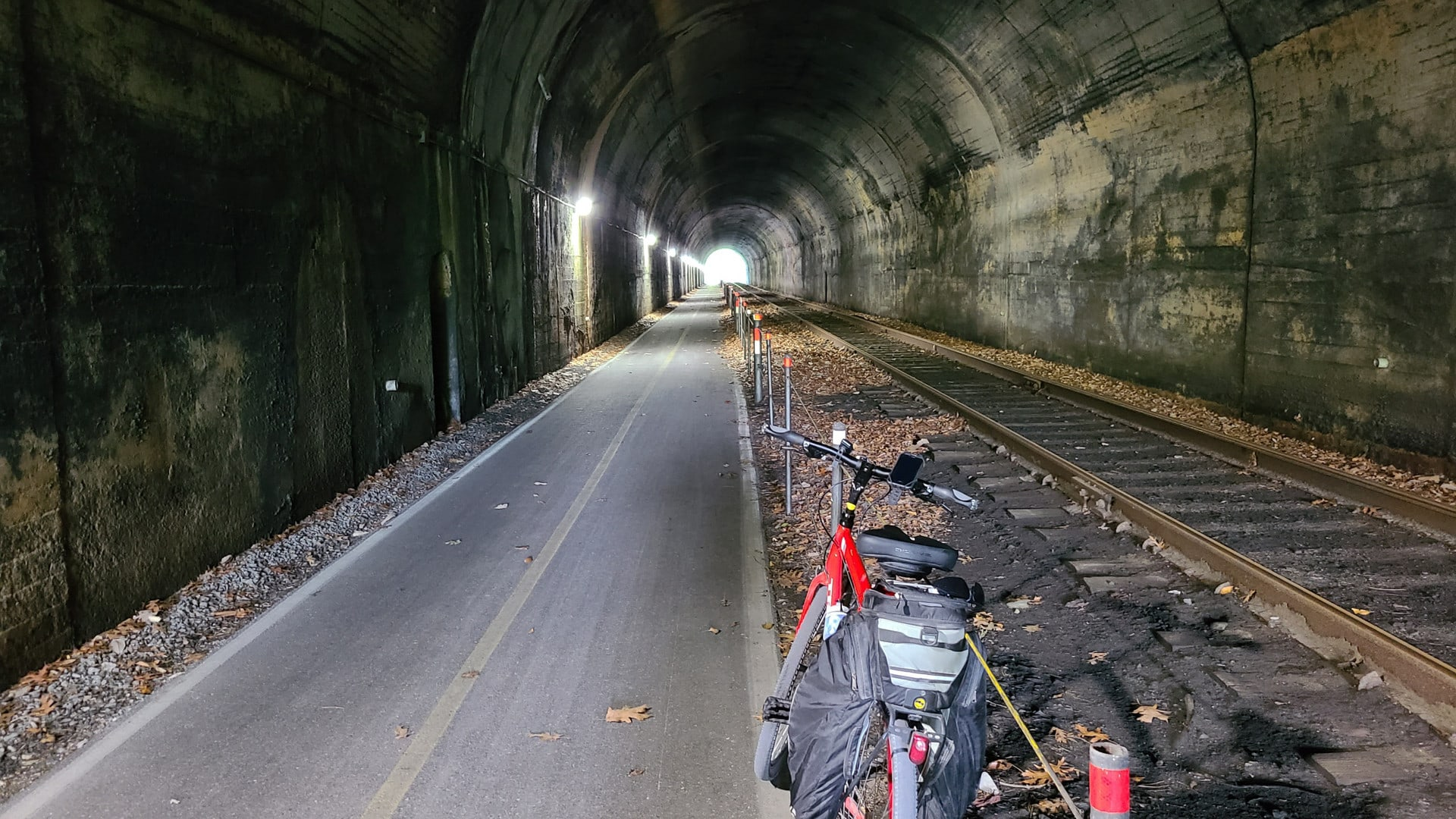 A red bike rests against a safety railing inside a well-lit tunnel. The trail is paved and a railroad track runs along the side.