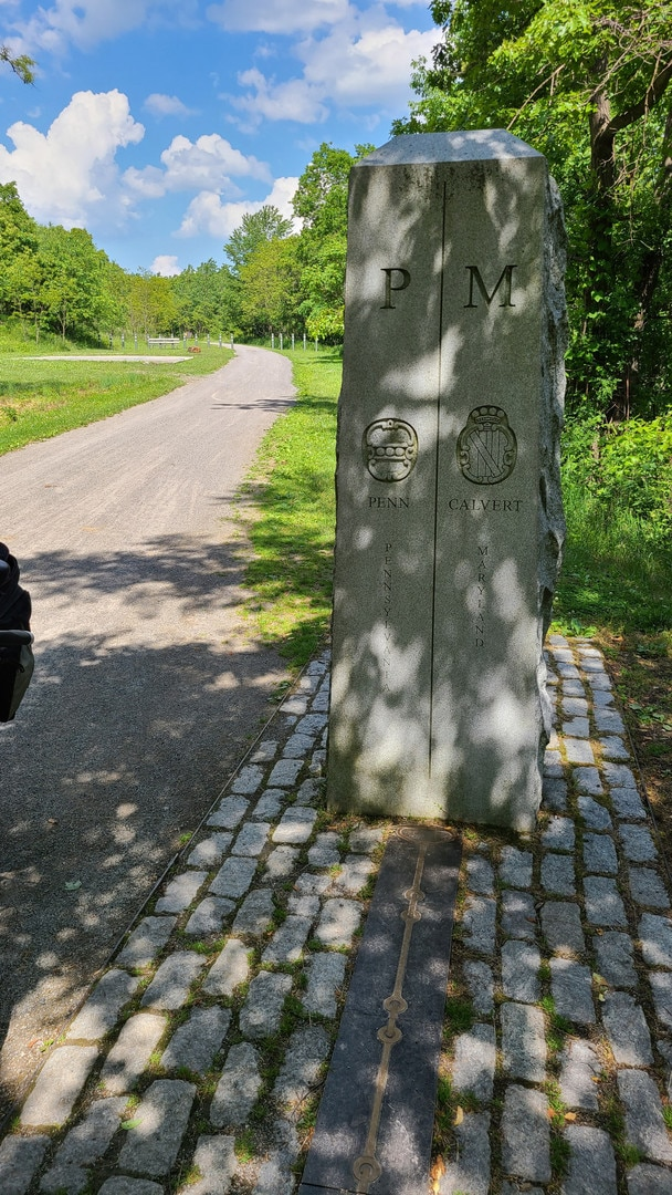 A stone monument marks the Pennsylvania-Maryland border. Metallic chain emblems are set in stone.