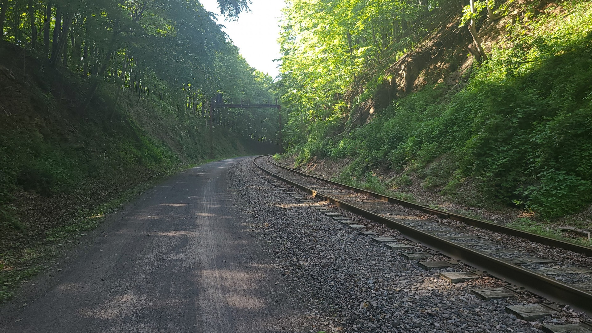 A crushed limestone trail follows a rail line through a small valley. Trees line either side. Old metal signaling equipment is visible in the distance.