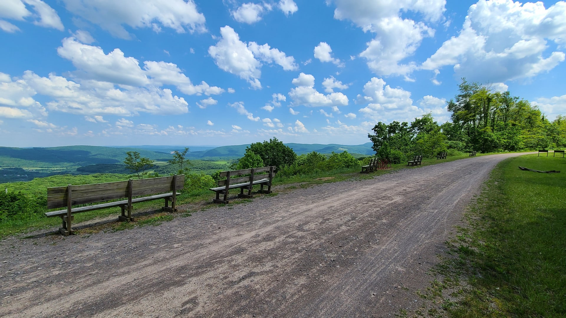 Fluffy clouds dot a beautiful blue sky. Benches line the path, looking out over a wide valley