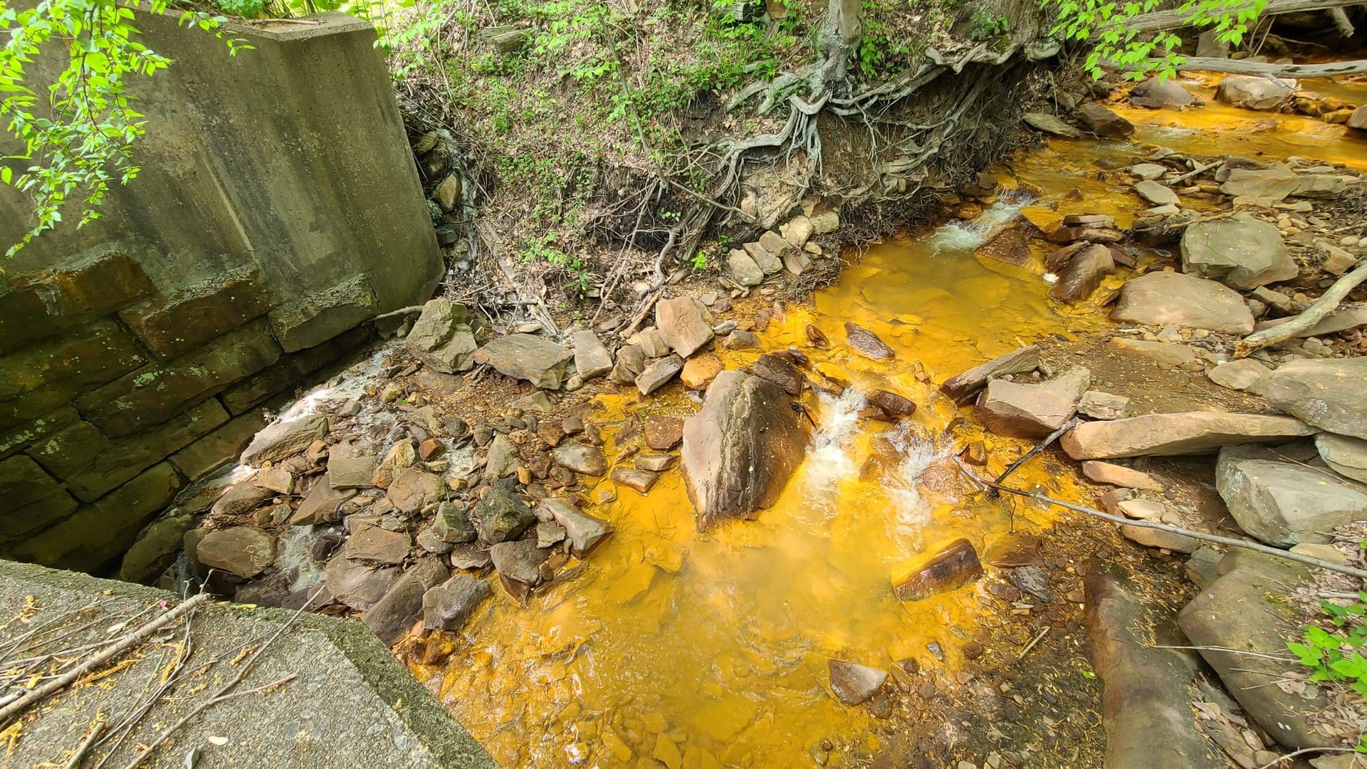 Polluted orange water flows through a stony creek. Chalky white water trickles in from the side.