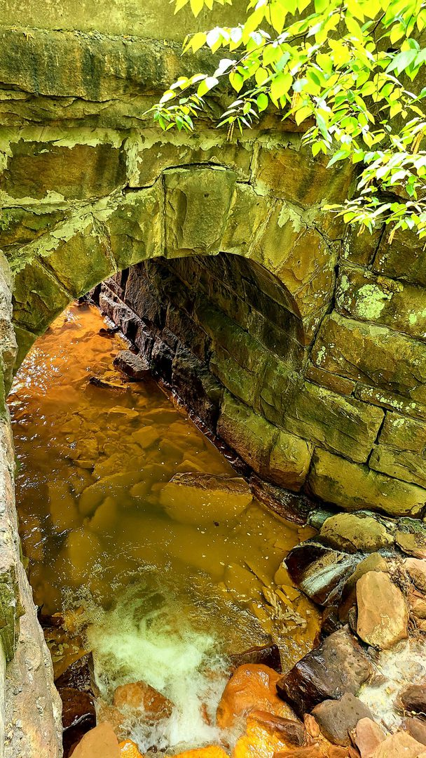 Orange polluted water flows through a channel under a small stone railroad bridge.