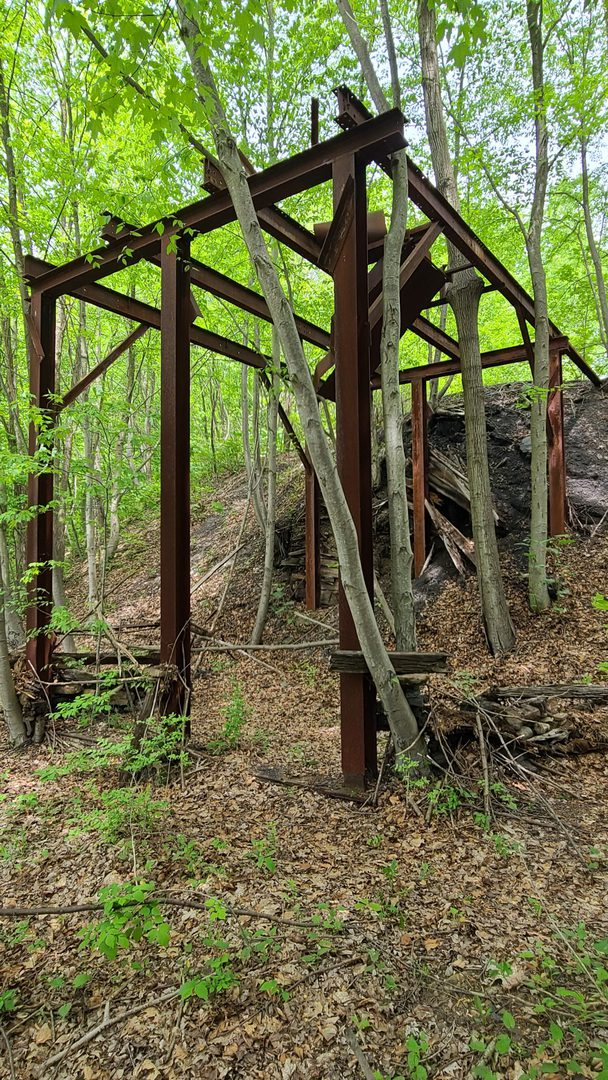 The rusty remains of an old coal tipple built with steel I-beams.