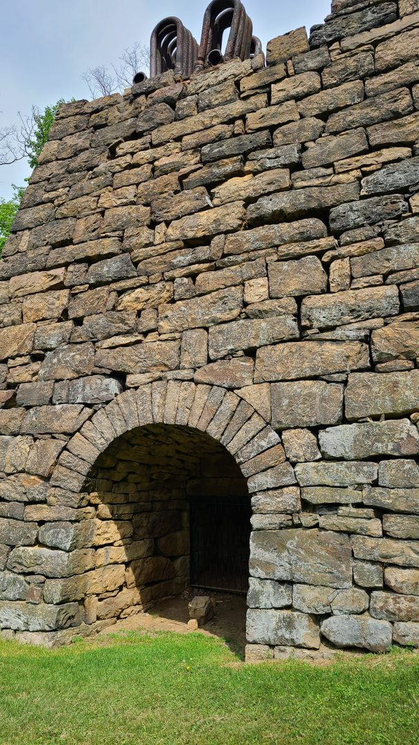 A stone archway leading into the heart of the furnace. Old rusty metal piping is visible on top.