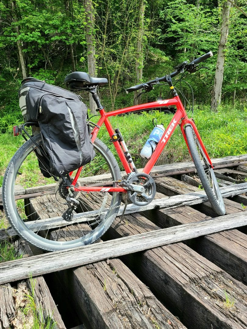 A red bike with panniers, a water bottle, and a tire pump sits on railroad ties with forest in the background.