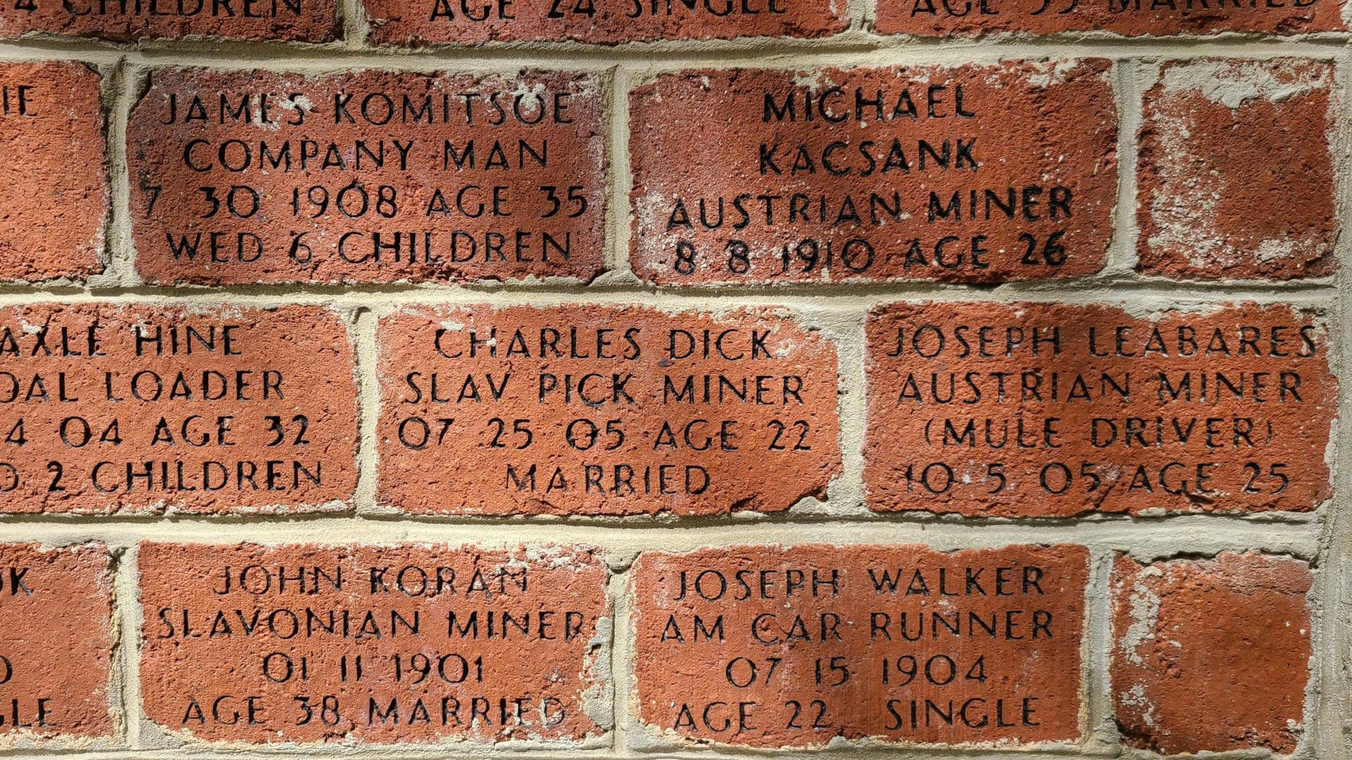 The names of coal miners are etched into a red brick memorial. The dates are from the early 20th century. The miners were all in their 20s and 30s.