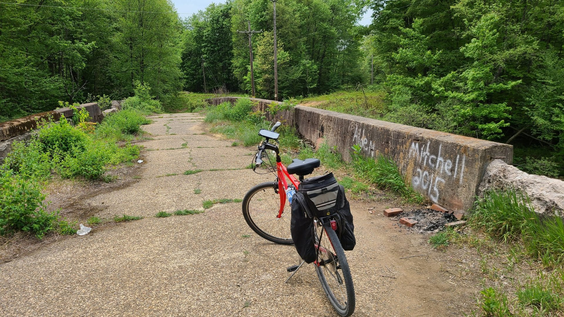 A red bike sits in the middle of a decaying concrete bridge, facing a clearing in the woods.