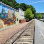 A railroad is bordered by a brick walkway on the left and a wide gravel bike path on the right. A mural next to the trail depicts the history of Glen Rock.
