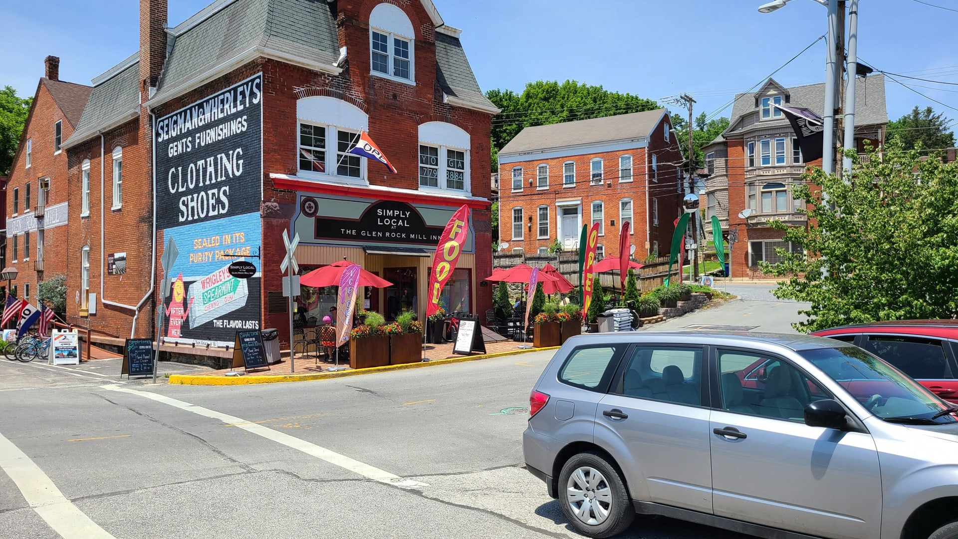 The Glen Rock Mill Inn sits on a street corner. Tables and umbrellas line the sidewalk. On the side is an old mural for Wrigleys Gum.