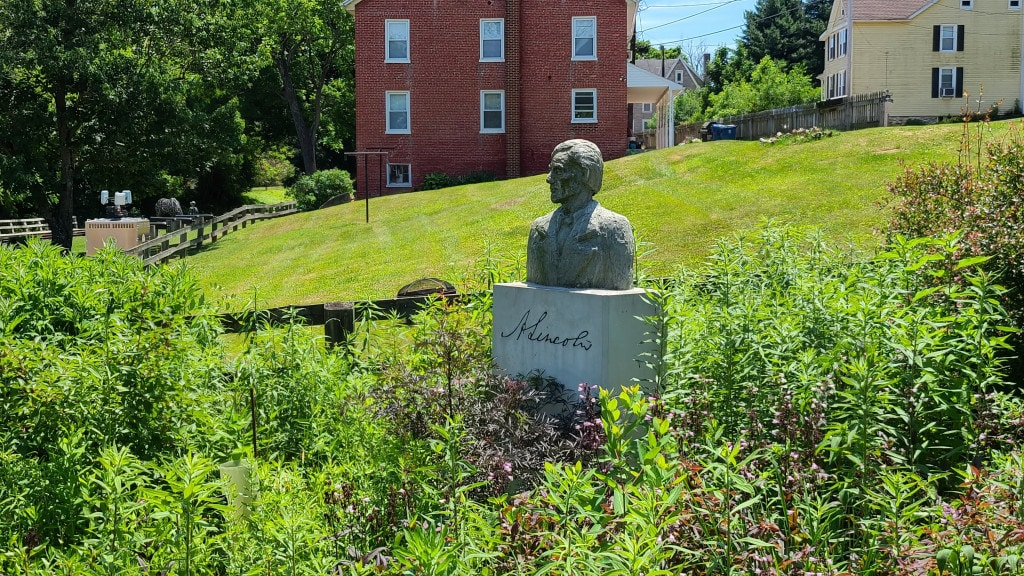 A bust of Abraham Lincoln sits in a garden, looking to his right
