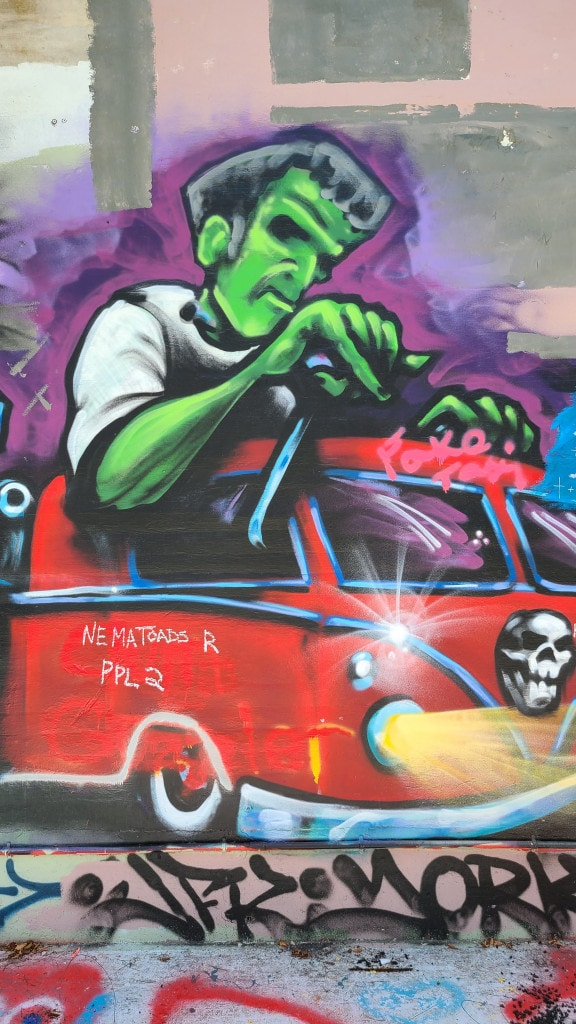 A graffiti art painting that resembles Frankenstein driving a red truck