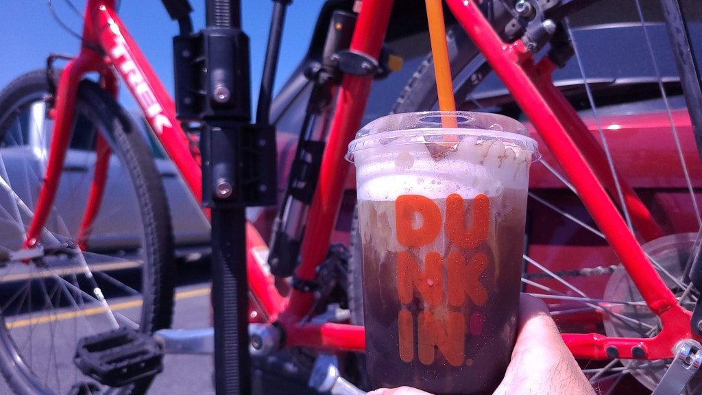 A hand holds a cup of iced coffee in front of a red Trek bike hanging on the back of a red SUV. The cup says