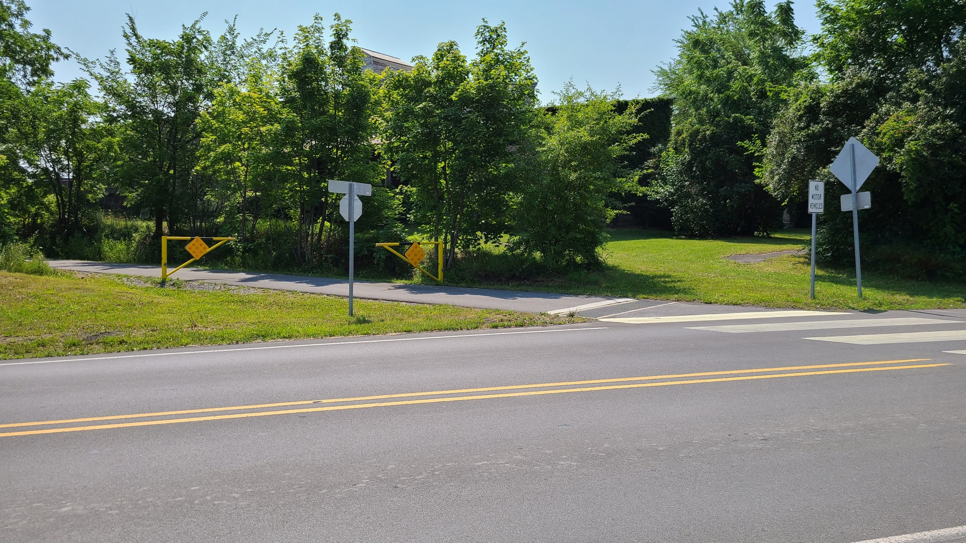 """A paved bike trail emerges from the woods and crosses the road at an angle. The trail's path across the road is marked with bold white stripes painted on the road. The bike trail has a stop sign, and a sign facing the road reads """"no motor vehicles""""."""
