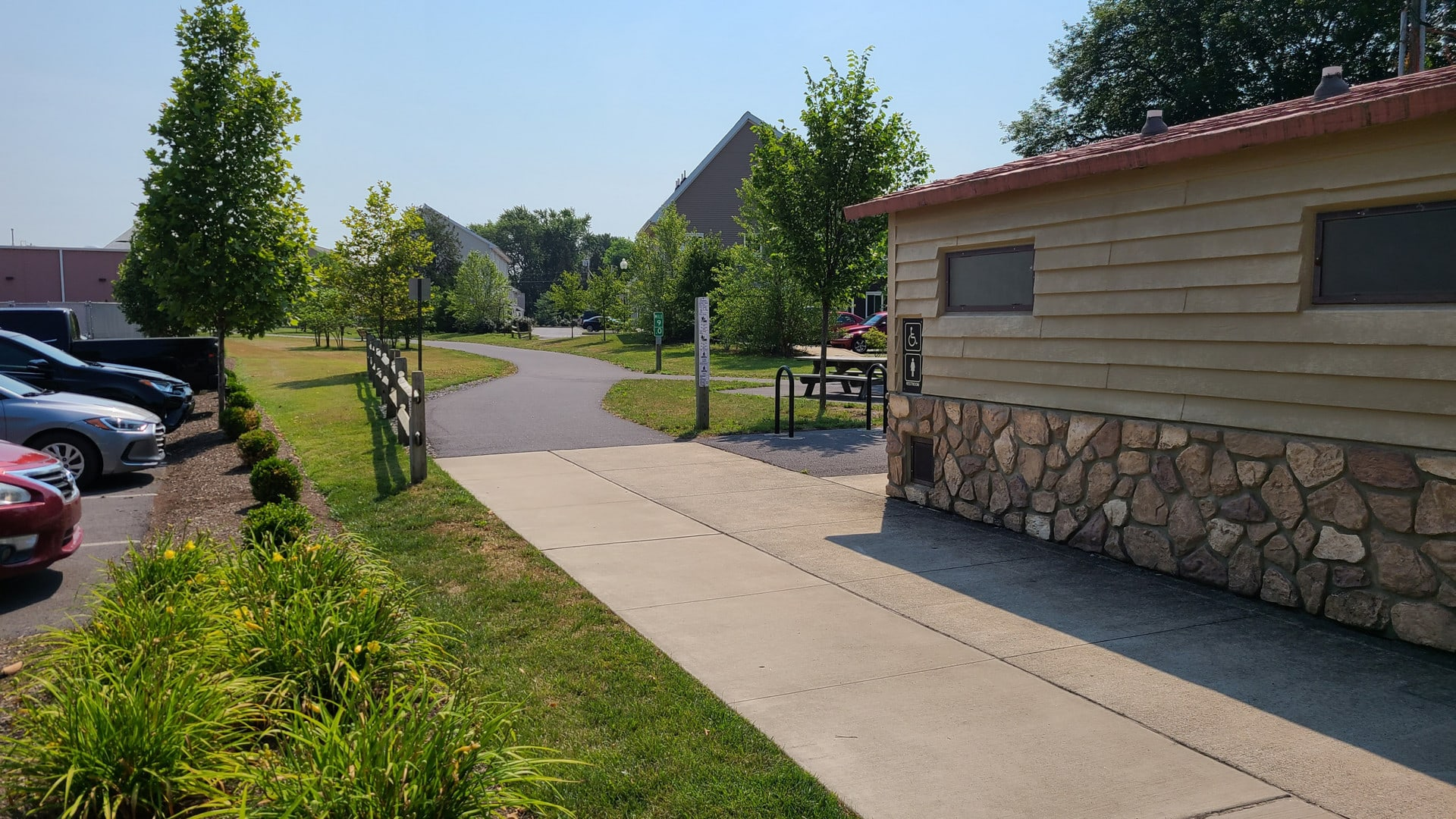 The trail runs past some public restrooms before snaking through a tree-lined development.