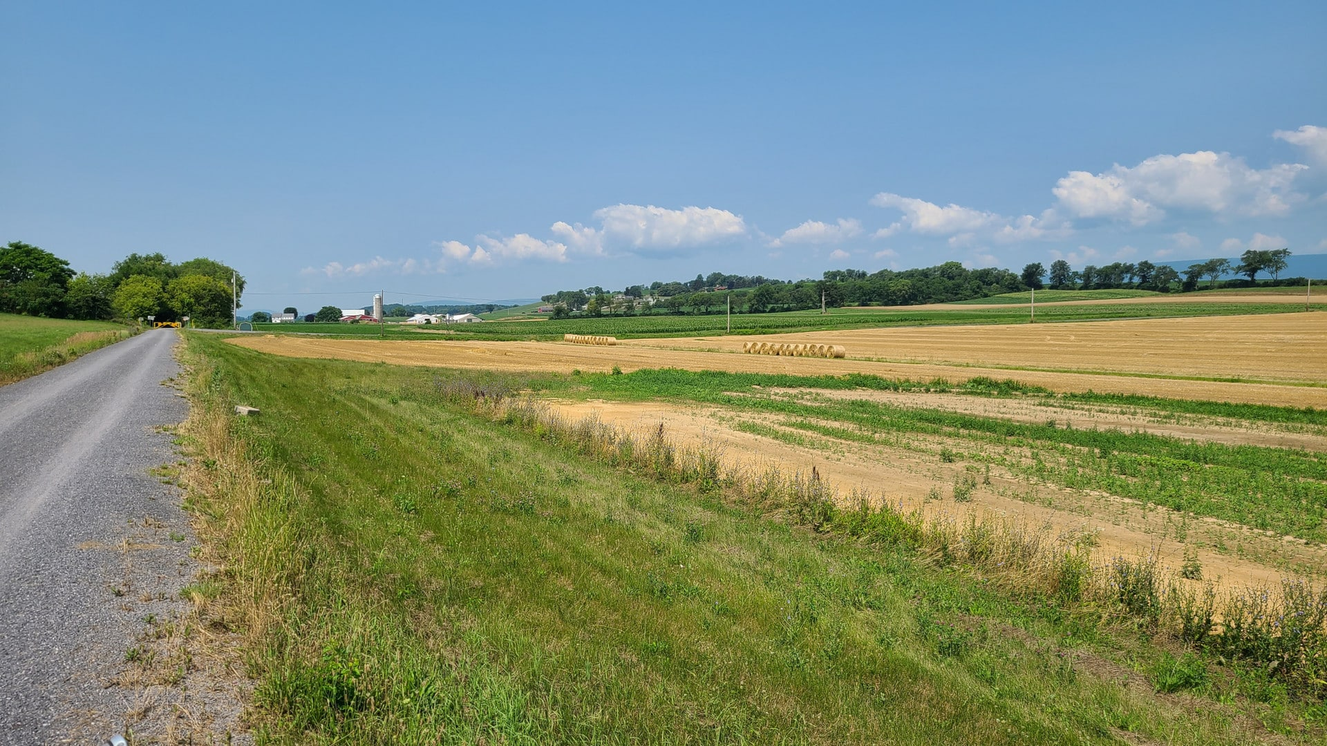 The gravel bike trail passes through a rolling farm field. Several dozen rolls of hay sit in the field, awaiting pickup. In the distance, a treeline marks the edge of the farm. A few fluffy clouds dot an otherwise clear blue sky.