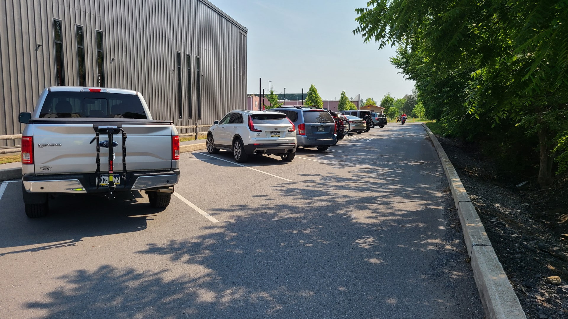 Vehicles are parked in a narrow parking lot. They include a silver Ford F150 pickup, a white Kia SUV, a blue minivan, a red SUV with a bike on the back, a white sedan, a blue Jeep Wrangler, and a motorcycle.