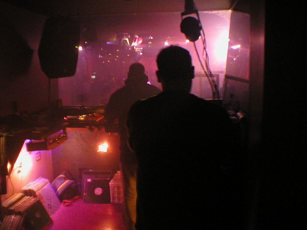 The view from a DJ booth, looking out across a dimly-lit sea of people