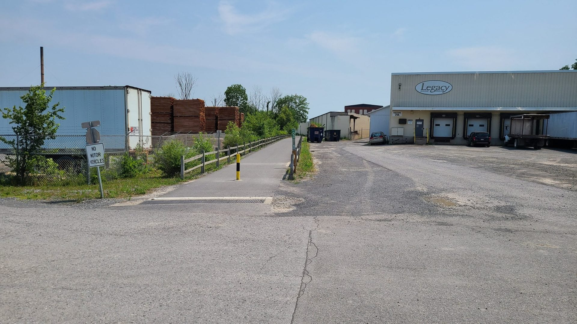 """The rail trail ends in paved parking lot. A wooden fence separates the trail from an industrial area consisting of several warehouses and wood piles. A sign reads """"no motor vehicles"""" and a green mileage marker reads """"0.0"""", signifying the beginning of the trail."""