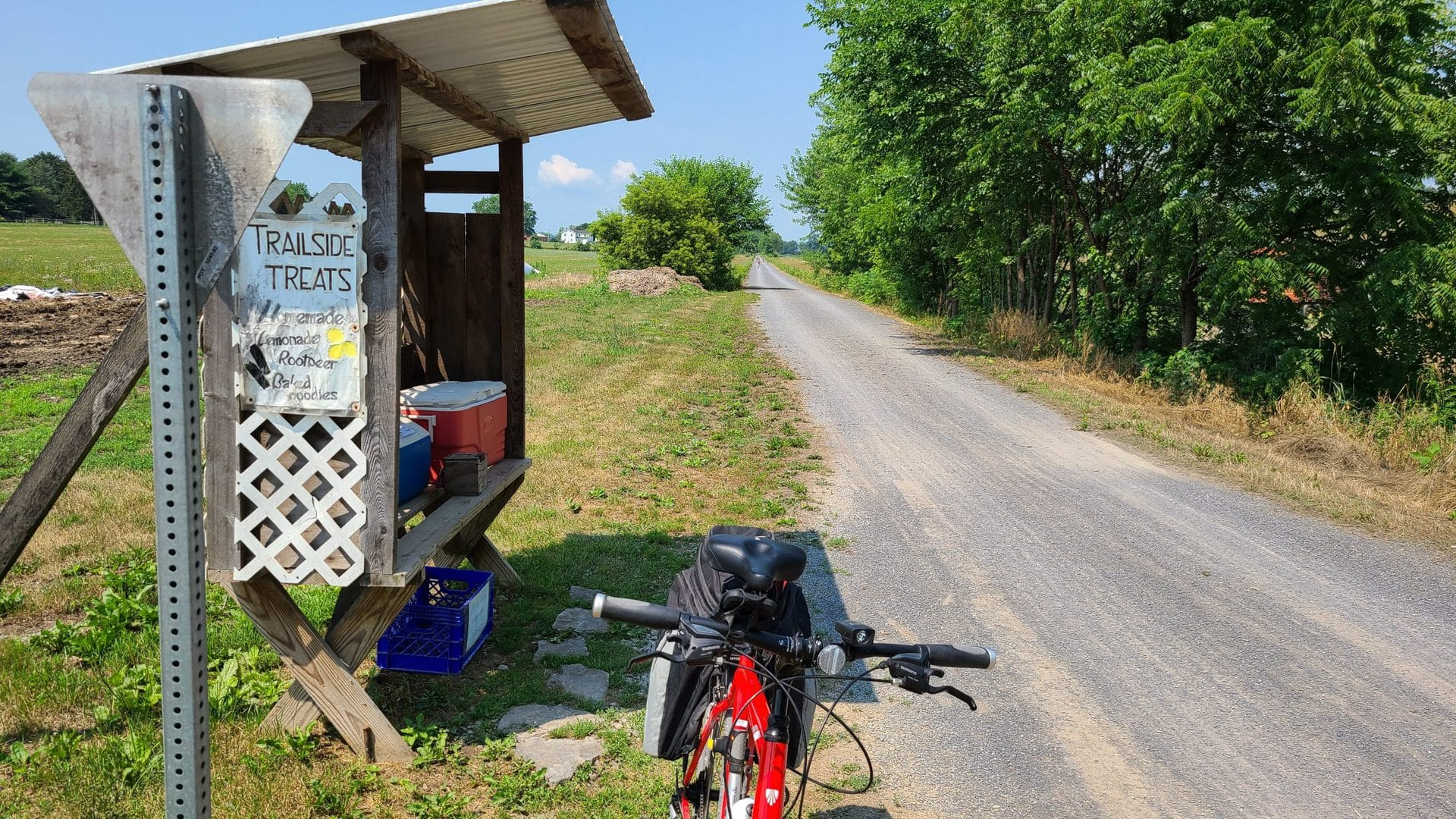 """A handmade foodstand sits about six feet off the trail. The stand contains several coolers of varying colors and sizes, each containing different snacks and beverages for sale. A sign reads """"Trailside Treats: Homemade lemonade, root beer, baked goodies"""". My red bike is visible in the foreground."""