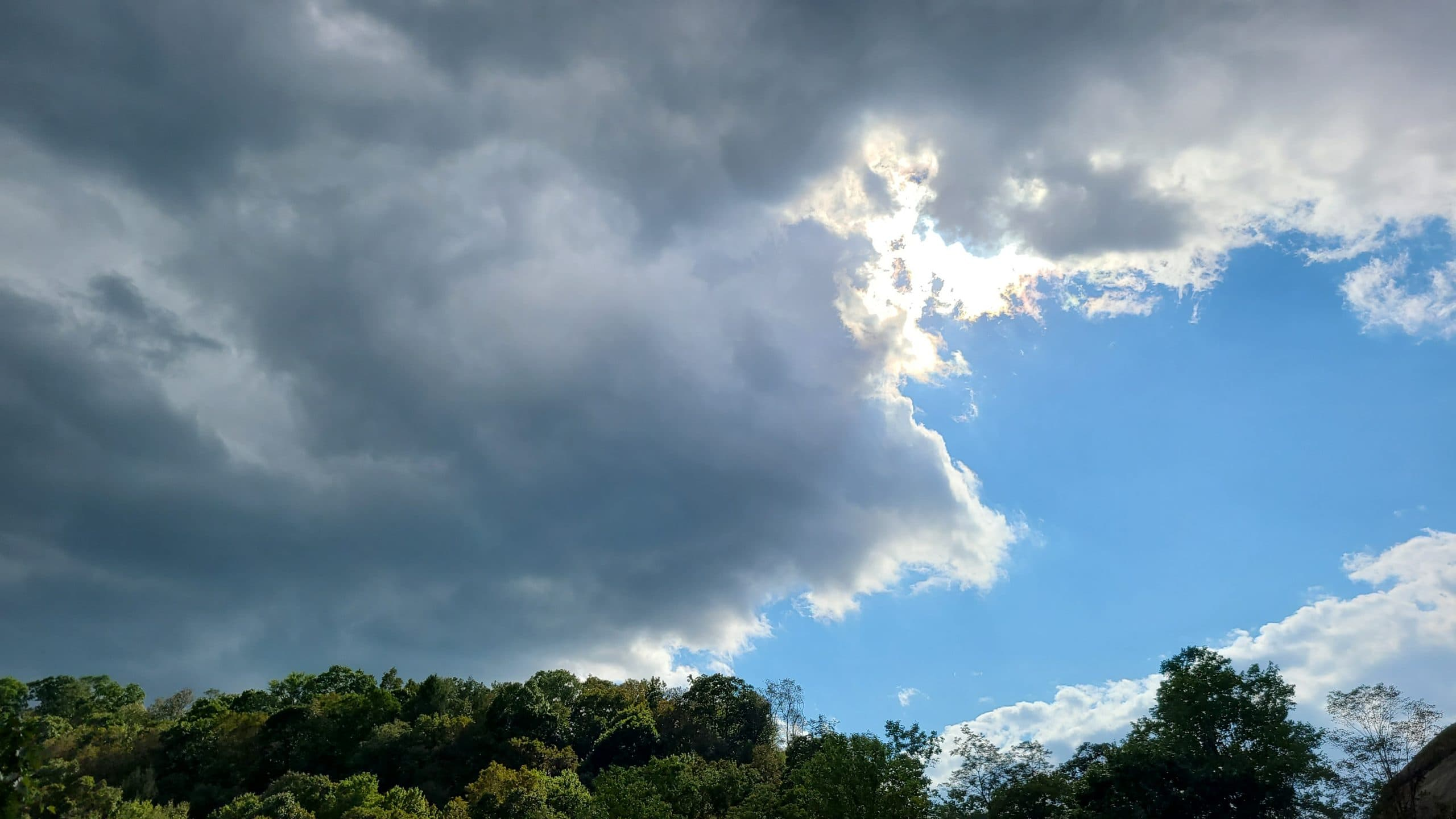 An ominous-looking dark cloud covers an otherwise sunny blue sky.