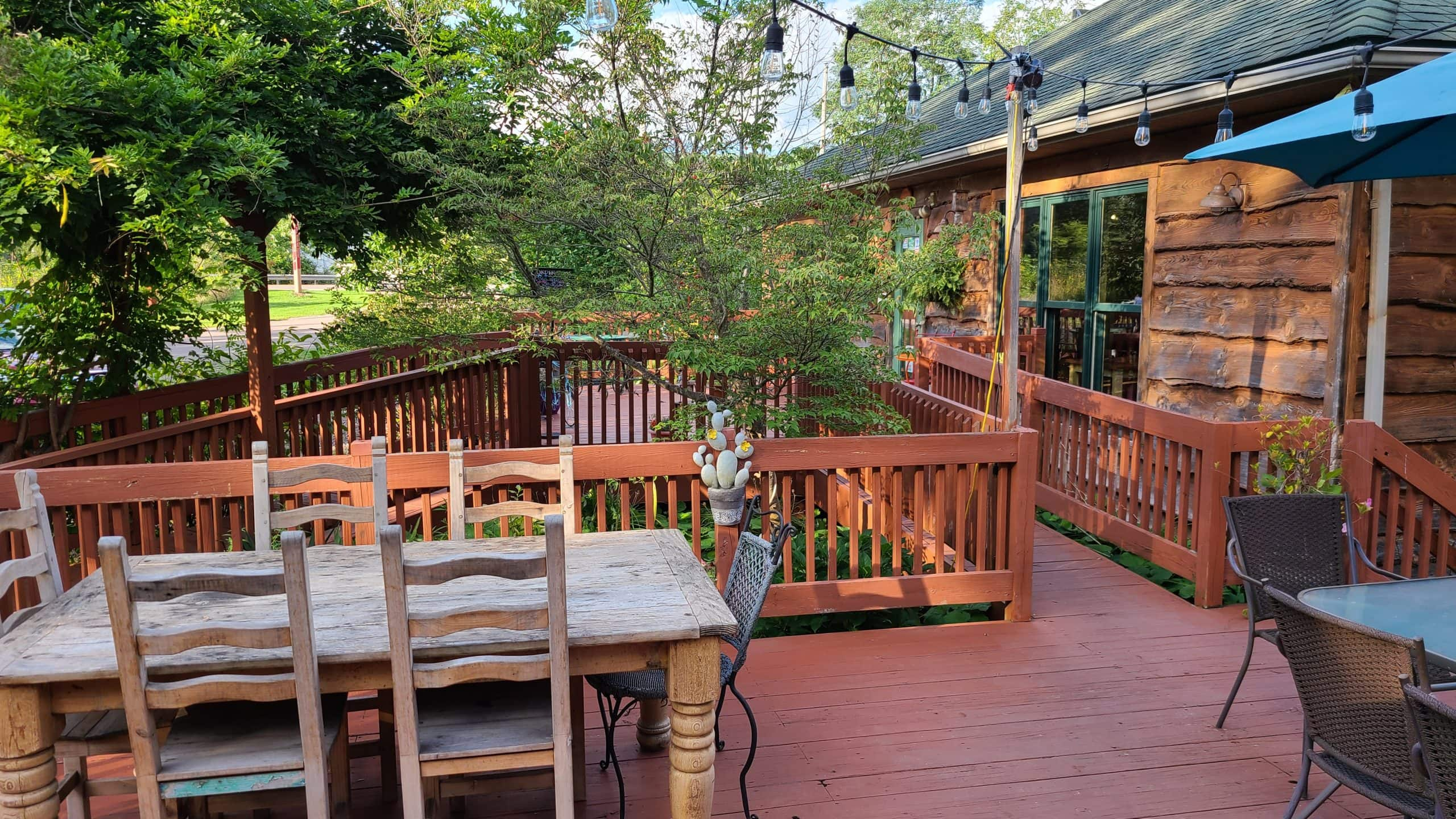 The Lucky Dog Cafe's outdoor seating area. Several tables sit on a wooden deck. Decorative lights hang above.
