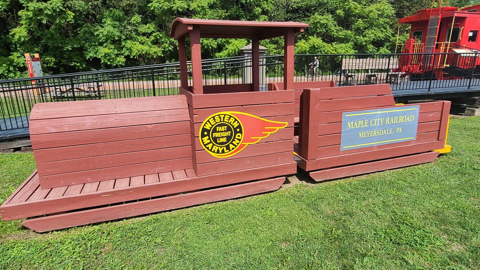 A wooden locomotive and coal car sits in a grassy playground. The locomotive is adorned with the logos of the Western Maryland railroad and Maple City Railroad.