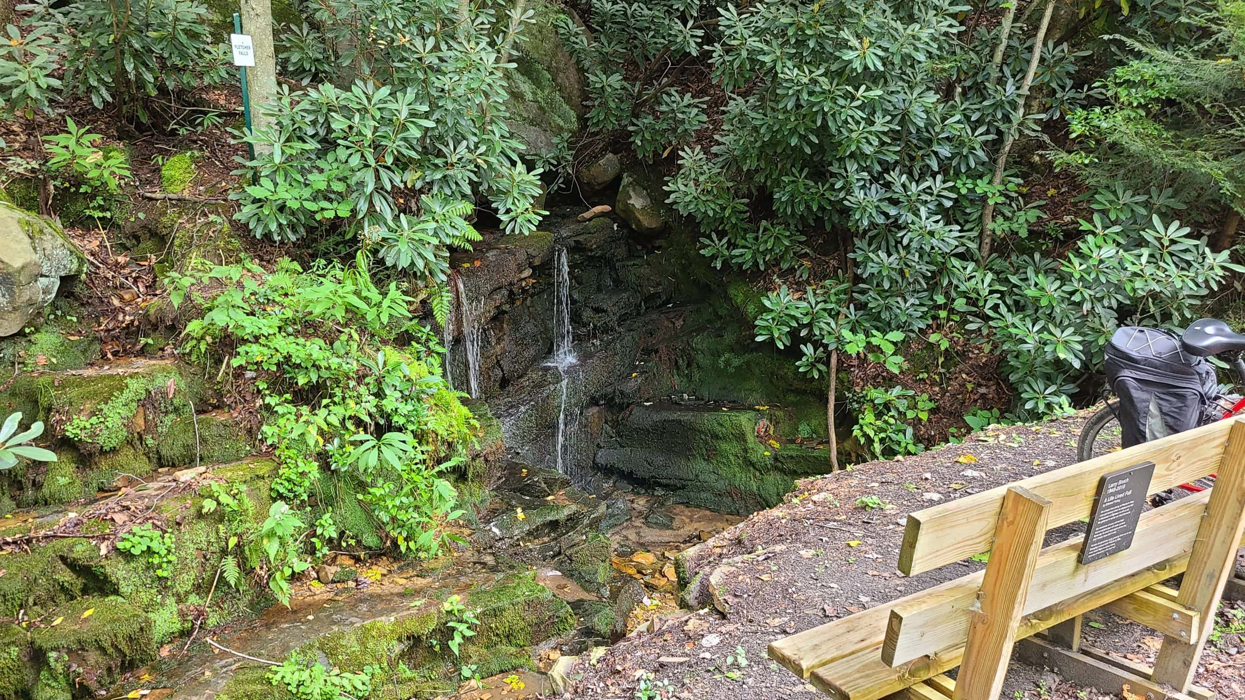 A small series of waterfalls is surrounded by lush vegetation and forest. A bench with an illegible sign provides a place to rest. A bike is visible.
