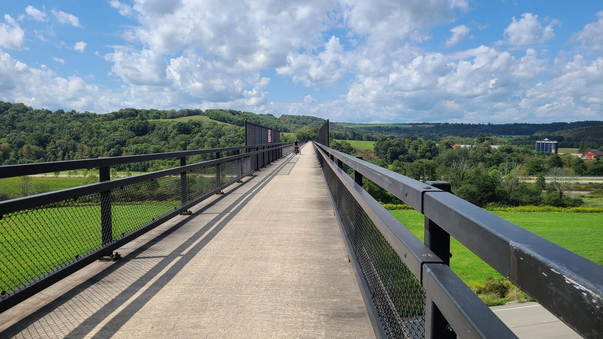 The trail uses a very long viaduct to cross over several highways and a railroad. Trees and hills dot the landscape.