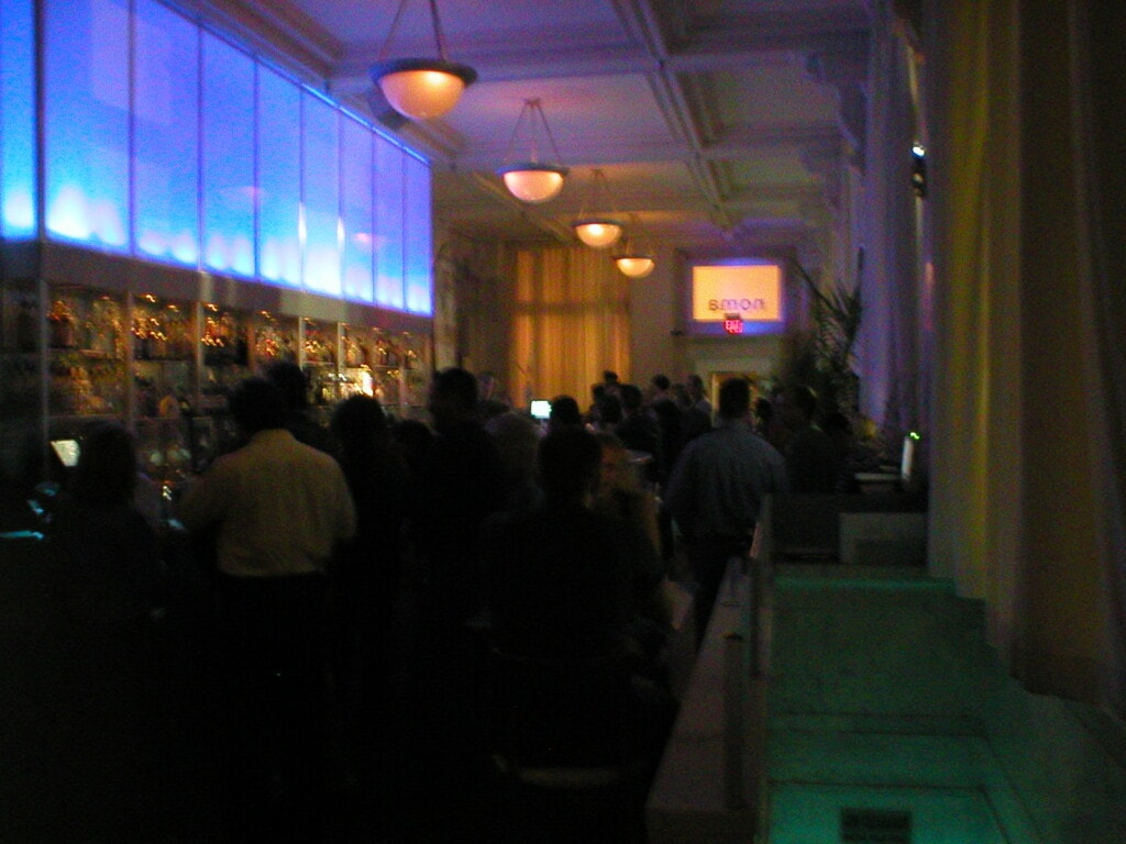 A crowded, dimly-lit lounge with blue lighting